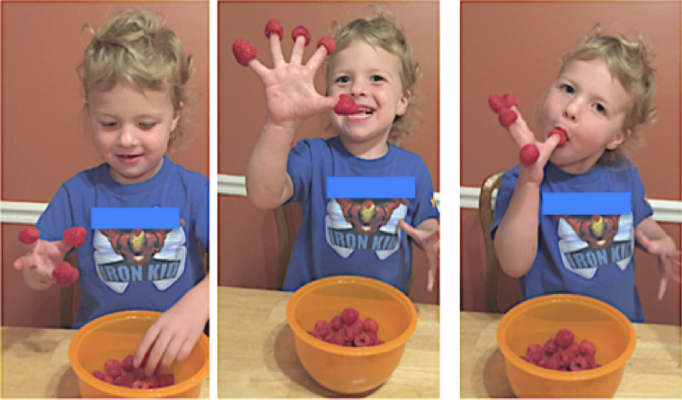 A young boy sticks raspberries on his fingers, then eats them.